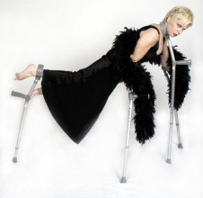 A photograph of a woman suspended horizontally on crutches wearing a black evening dress and feather boa.