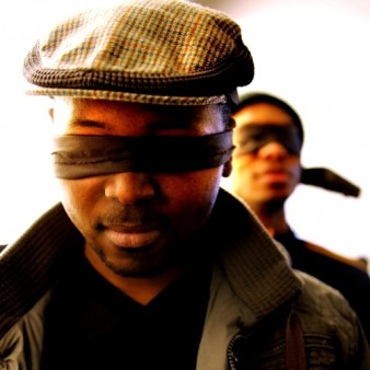 two men in blindfolds one standing behind the other
