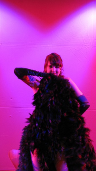 photo of a female burlesque performer with a fan of black feathers against a pink background