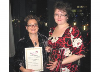 two women hold a certificate and a trophy
