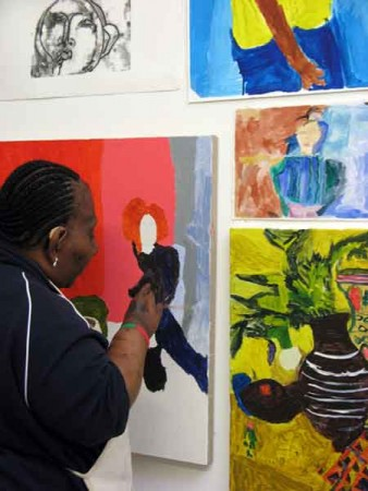 Photo of artist Mawuena Kattah in the studio, looking at artwork on the wall Mawuena Kattah and Intoart