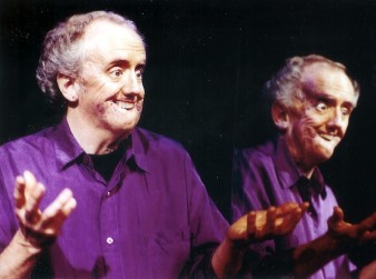 actor david roche, dressed in a purple shirt, performs in front of a mirror