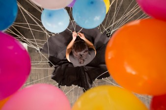 A photograph of Noëmi Lakmaier performing 'Never Happier'. It shows a shot of her head from above with various multicoloured balloons floating above it which are attached to her skirt.