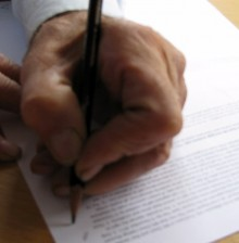 Image of a hand writing on a piece of paper with a fountain pen