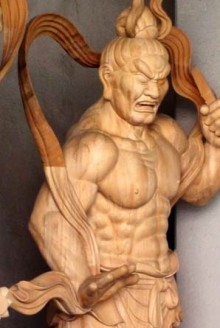 Wooden statue of a warrior figure with muscled torso, held in a dramatic pose