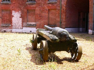 Photograph with a cannon in the foreground, and a brick built Victorian fort in the background