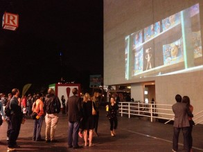 People gathered in a pedestrianised area staring up at a projection on a big wall