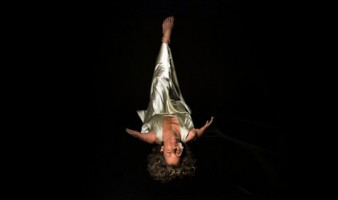 a woman in a silver dress is suspended upside down against a black background