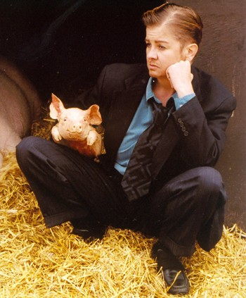 photo of actor dressed in a suit and tie, holding a baby pig