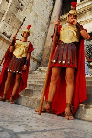 photo of two men dressed as roman centurions looking downwards at the photographer