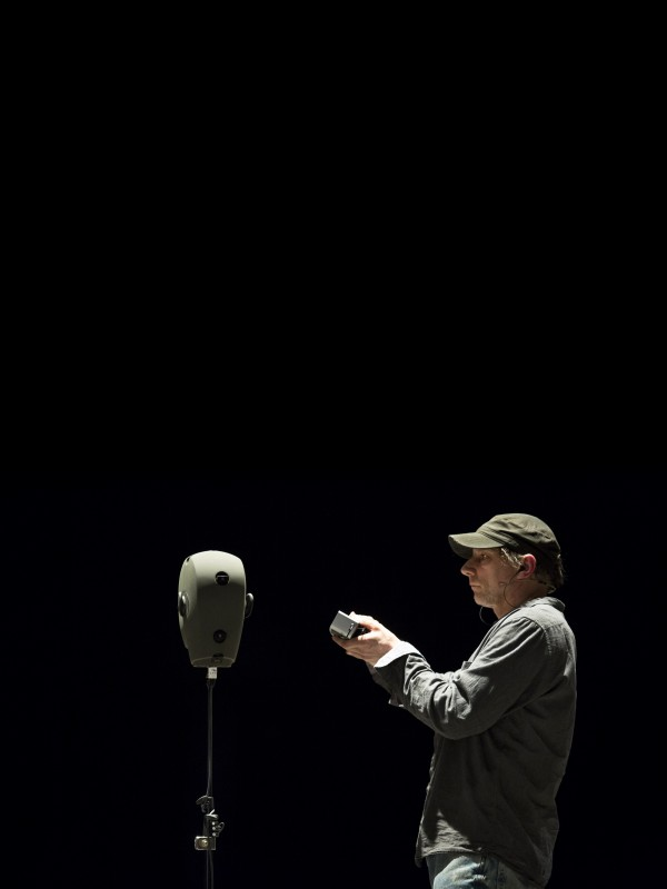 Performer, Simon McBurney holds a device up to a mannequin's head, amidst a black background.