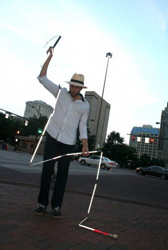 photo of the artist Carmen Papalia folding a 20 foot long white cane with red markers as part of a live performance art piece