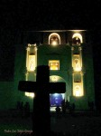 Granja's photograph shows a religious building at night. Statues are placed within arched windows and illuminated with golden light. The surrounding space is deep and black.