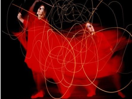 a digitally manipulated image of a female dancer moving in a swirl of red and lines of light