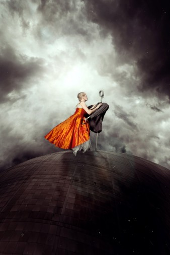 a performer in a red dress is pictured above a building against a stormy sky, dancing with a partner made with crutches