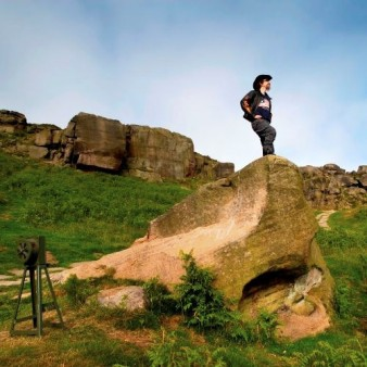 a man dressed in black stands on a rock on the moors