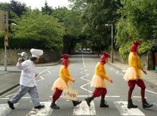 photo of actors dressed as chickens crossing a road