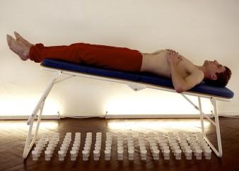 Photo of performance artist lying down on an upraised platform