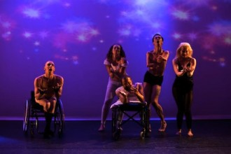 five members of the cast of In Water I'm Weightless face the audience on stage against a purple-lit background