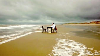Still image from 'The Sea Reminds Me' showing a man sat at a desk on the edge of the sea on a sandy beach