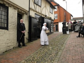 still from the Oyster Project's film 'Timeslip' showing a Victorian gent on a cobbled street bearing a stick as a young woman walks away