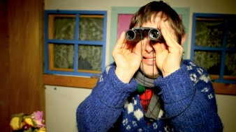 still of a man in a blue jumper looking through binoculars