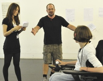 two young people listen to instruction during a drama workshop