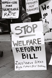 black and white photo from the action of a protestor behind a placard which reads 'Stop Welfare Reform Bill. Zacchaeus 2000 single mothers self defence'