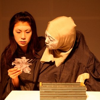 a woman and life-size puppet both gazing intently at an object