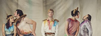 Still image of dancers in colourful costume from the touring production Artificial Things