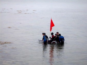 a photograph of a woman in a wheelchair being carried through the water by a group of people