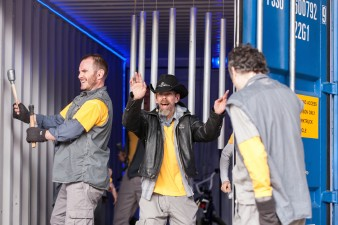 photo of Jez Colbourne wearing a yellow raincoat and a leather hat, standing in the open doors of a large shipping container with two other performers
