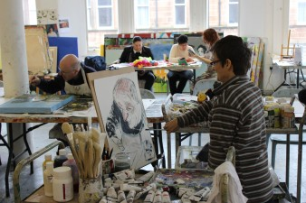Artist Tanya Raabe-Webber stands at artists easel painting a portrait of a man engaged in his own arts activity in a large art studio classroom