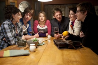 photo of a group of actors sitting at a dining room table