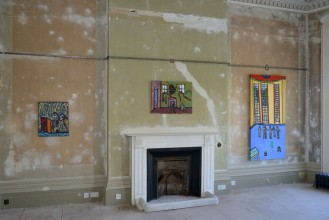 Exhibition shot from 'Home Away from Home' by Thompson Hall, it depicts three paintings above an ornate fireplace. The room is otherwise bare and derelict condition with plaster marks on the walls.