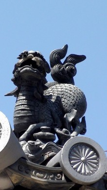 photo of a stone lion decorating a rooftop, against a blue sky