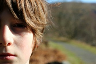 close-up of a boys face against a blurred background of a lane bordered by trees