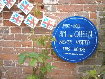 blue plaque on a wall next to bunting  reading HM The Queen Visited This House
