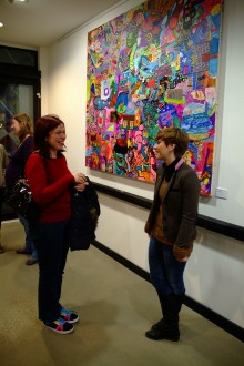 Visitors and staff at the Art House with work by artist Ivan Liochev
