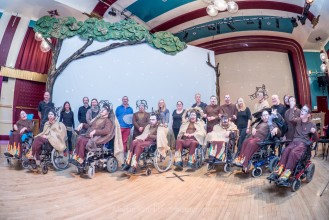A photograph of the cast and crew of CEDA's production of Clive Essame's play, Impisi. It shows many actors in wheelchairs and others standing on a theatre set.