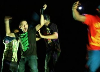 photo of four young guys dancing really hard and one in the centre has a nike t-shirt by Jon Pratty/dao