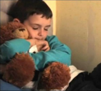 still from gary thomas film the dog and the palace of a young boy cuddling a teddy bear