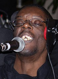 A young black man sings into a microphone