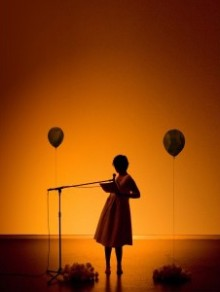 in a warm orange glow Kat, in a loose A-line dress, stands almost a silhouette, before a microphone with a balloon on each side of her