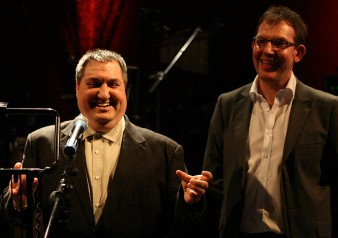 two men wearing suits and white shirts stand on stage and are smiling to the audience