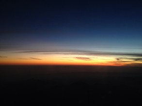 Orange sunset taken over silhouetted desert from airplane