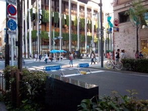 A sunny-day photo of one of the main roads through Ginza, closed to traffic for several hours each weekend. Blue garden umbrellas, tables and occupied chairs in the middle of the road. A tall glass building with slim, white, vertical stripes of concrete,