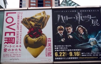 Photo of double poster for exhibitions at the Mori Art Museum Gallery; with Jeff Koon's gold and red Sacred Heart on the left and a Harry Potter image of the three main children and owl on the right.