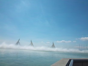 A very blue image of water and sky; water, the infinity pool, taking up the bottom third of the view. The mist fountains mask the horizon and melt into the low lying white cloud. Three white masts with white sails are just visible peeking above the mist a