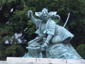 Bronze statue on a stone plinth, depicting a Kabuki actor in heavy and elaborate costume, crouching with weapon in hand